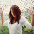 Beautiful woman in white dress posing holding metal mesh — Stock Photo