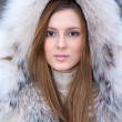 Beautiful young woman in winter fur coat — Stock Photo
