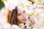 Young woman enjoying smell of blooming tree — Stock Photo