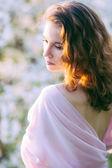 Young beautiful woman in blooming gardens — Стоковое фото