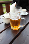 Beer mug on a table in a city restaurant outdoor — Stock Photo
