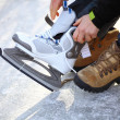 Stock Photo: Tying laces of ice hockey skates skating rink