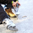 Стоковое фото: Tying laces of ice hockey skates skating rink