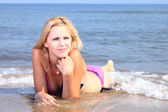 Beautiful woman in bikini sunbathing seaside — ストック写真