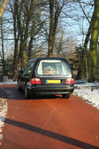 Hearse on a winter cemetery — Stock Photo