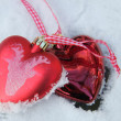 Red and white heart ornaments in snow — Zdjęcie stockowe