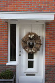 Modern door with christmas wreath — Stockfoto