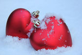 Two red hearts in the snow — Stock Photo