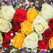 Yellow, white and red roses in a wedding arrangement — Stock Photo #25590557