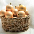 Golden Christmas ornaments in a wicker basket — Stockfoto #26071333
