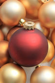 Red ornament on a pile of golden ornaments — Stock Photo