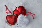 Red and white heart ornaments in snow — Stock Photo