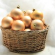 Golden Christmas ornaments in a wicker basket — Stok Fotoğraf #26186327