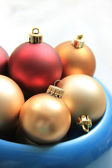 Red and golden christmas ornaments in a blue bowl — Stock Photo