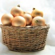 Golden Christmas ornaments in a wicker basket — Stok Fotoğraf #26810423