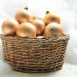 Golden Christmas ornaments in a wicker basket — Stock Photo #26810423