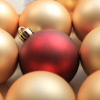 Red ornament on a pile of golden ornaments — Stock fotografie