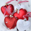 Red and white heart ornaments in snow — Stock Photo #30566255