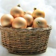 Golden Christmas ornaments in a wicker basket — Foto de Stock