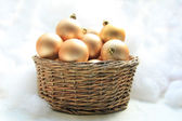 Golden Christmas ornaments in a wicker basket — Stock Photo