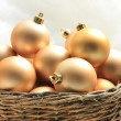 Golden Christmas ornaments in a wicker basket — Photo