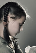 Sad little girl with toy on grey background — Stock Photo