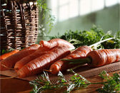 Carrots and basket in kitchen — Stockfoto