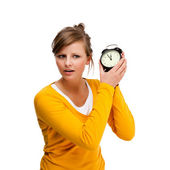 Young woman holding alrm clock isolated on white — Stock Photo