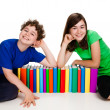 Kids behind pile of books isolated on white background - Stock Photo