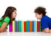 Kids behind pile of books isolated on white background — Stock Photo