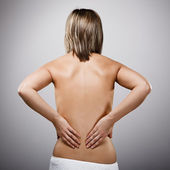 Woman massaging pain back — Stok fotoğraf