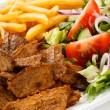 Grilled meat with French fries and vegetables — Stock Photo