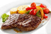 Grilled steak, baked potatoes and vegetables — Stock Photo