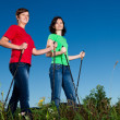 Nordic walking - active women exercising outdoor - Stock Photo