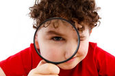 Boy looking through magnifying glass isolated on white — ストック写真