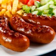 Grilled sausages, French fries and vegetables - Foto Stock