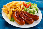 Grilled sausages, French fries and vegetables — Stock Photo