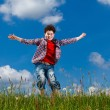 Boy jumping, running against blue sky — Stockfoto