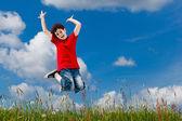 Atlama, mavi gökyüzü karşı çalışan bir çocuk — Stok fotoğraf