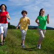 Active family - mother and kids running outdoor — Stok fotoğraf