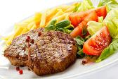 Bifes grelhados, batata frita e legumes — Fotografia Stock
