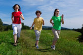 Active family - mother and kids running outdoor — ストック写真