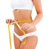 Woman measuring her slim body isolated on white background — Stock Photo