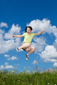 Girl jumping, running against blue sky — Stock Photo