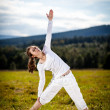 Woman exercising yoga outdoor - Stock Photo