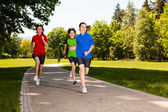 Active family - mother and kids running outdoor — Stock Photo