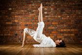 Woman exercising yoga against brick wall — Stock Photo