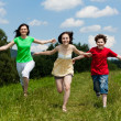 Royalty-Free Stock Photo: Active family - mother and kids running, jumping outdoor