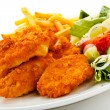 Fried chicken nuggets, French fries and vegetables — Stock Photo