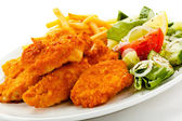 Fried chicken nuggets, French fries and vegetables — Stockfoto
